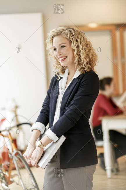 Portrait of smiling businesswoman with a meeting in background