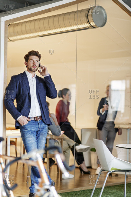 Businessman on cell phone in office with a meeting in background