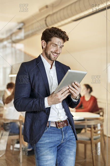 Smiling businessman using tablet in office with a meeting in background