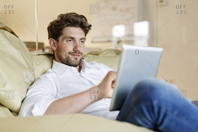 Smiling man in office using tablet in bean bag