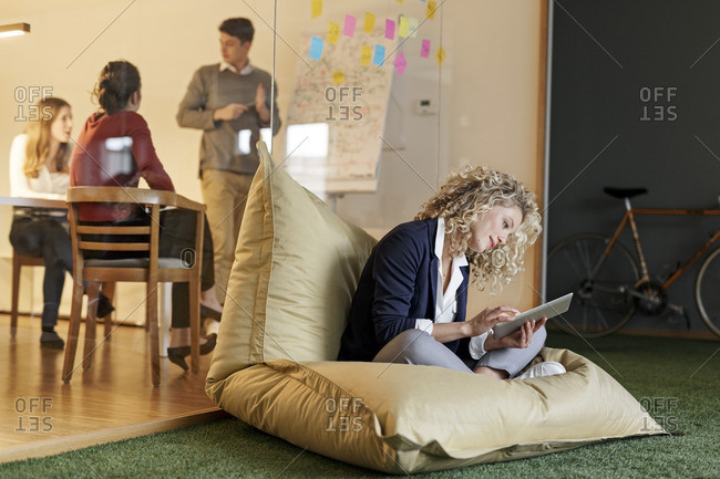 Woman in office using tablet in bean bag with meeting in background