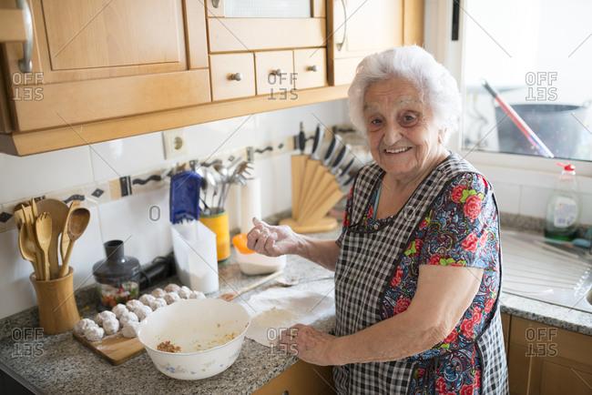 Portrait of smiling senior woman preparing meatballs in the kitchen