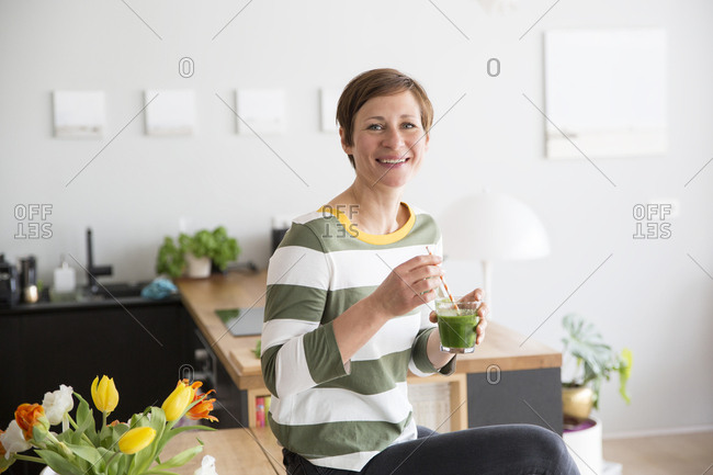 Portrait of smiling woman with green smoothie in the kitchen