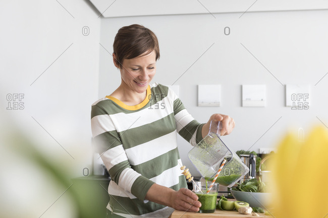 Smiling woman pouring green smoothie into a glass