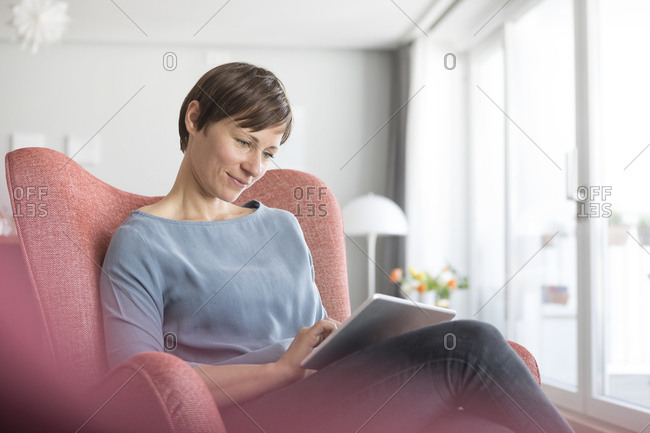 Portrait of woman sitting on armchair at home using tablet
