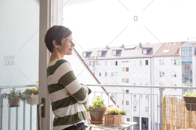 Smiling woman standing on balcony looking at distance