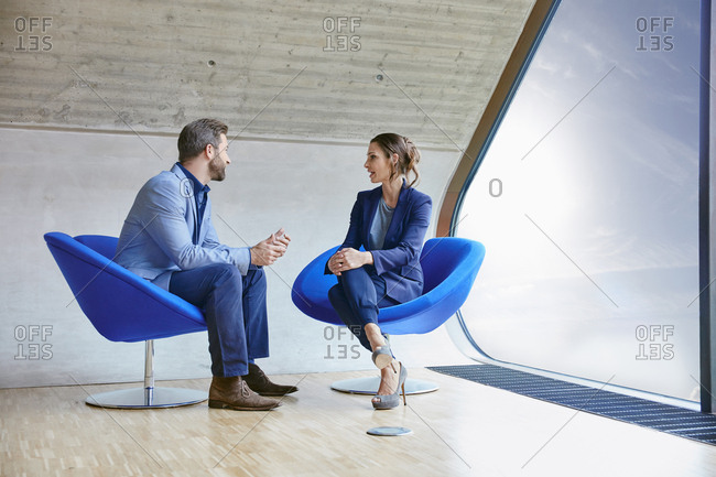 Man and woman sitting on chairs talking