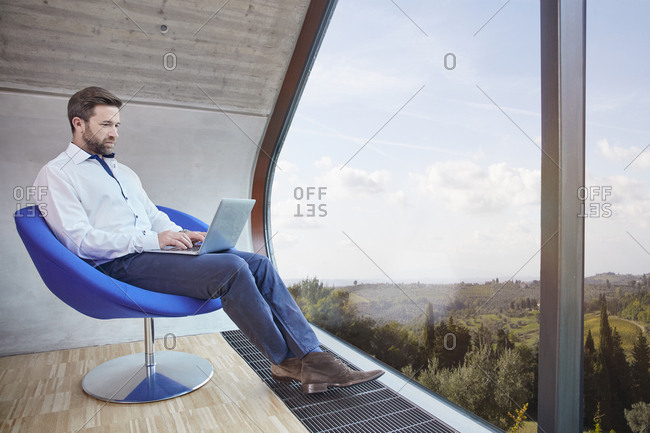 Businessman sitting on chair in attic office using laptop