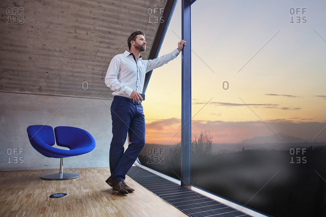 Businessman in attic office looking out of window at sunset