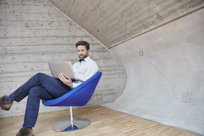 Businessman sitting on chair using laptop