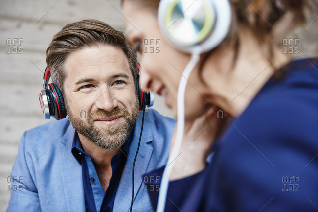 Man and woman listening to music with headphones