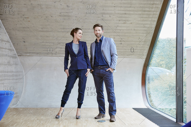 Portrait of man and woman standing in attic office