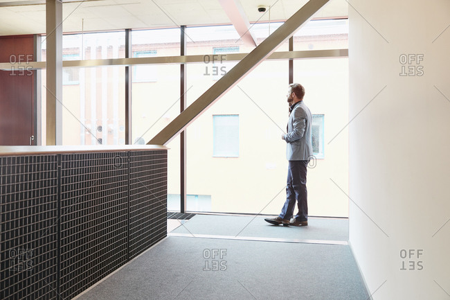 Businessman standing on office floor looking out of window