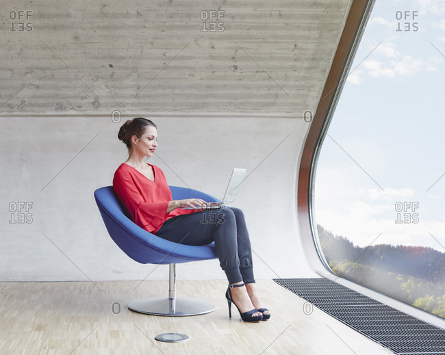 Woman sitting on chair in attic office using laptop