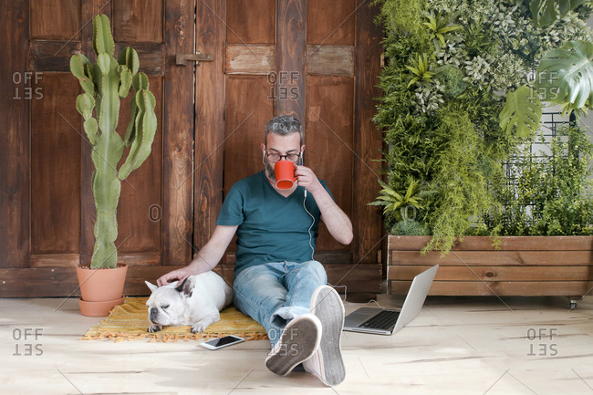 Bearded man sitting with his dog on the floor at home drinking coffee