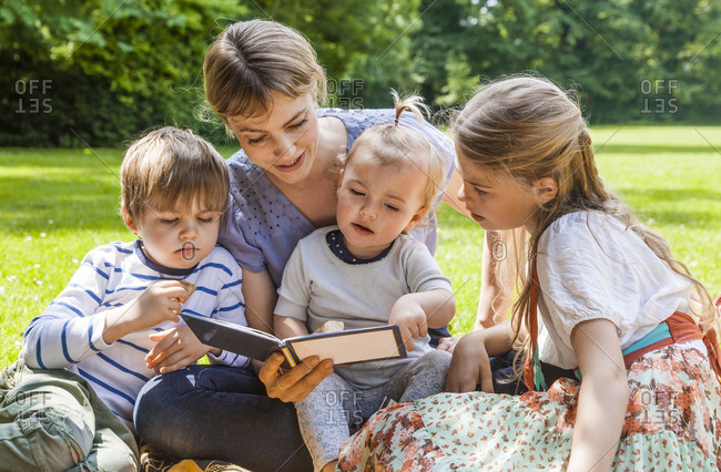 Mother showing photo album to children on meadow
