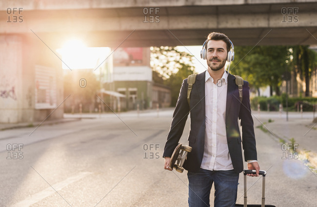 Young man on the move with skateboard- rolling suitcase and headphones