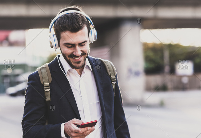 Smiling young man wearing headphones checking cell phone