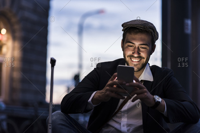 Smiling young man in the city checking cell phone in the evening