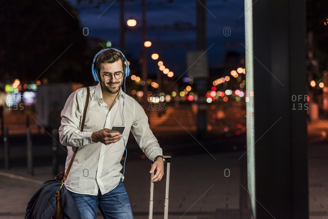 Young man in the city with headphones and cell phone at night