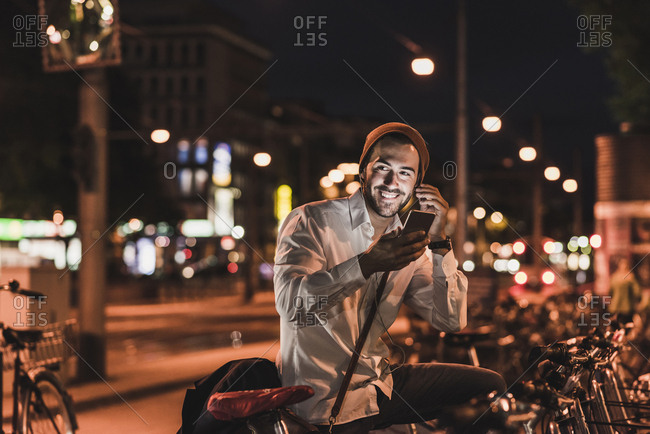 Young man in the city with earphones and cell phone at night