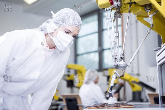Woman in factory examining robot handling cookies