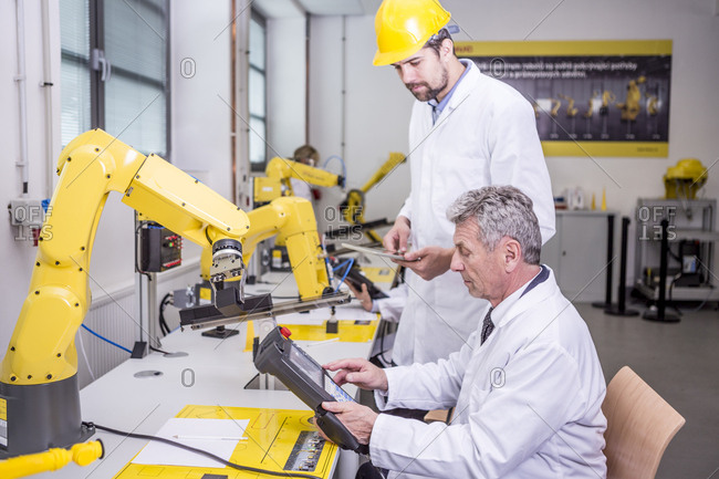 Two engineers in factory looking at device