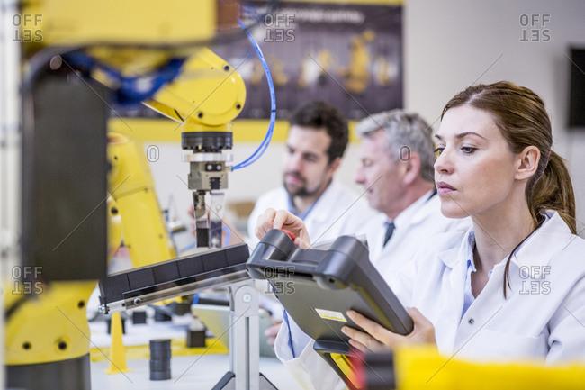 Engineers examining industrial robots