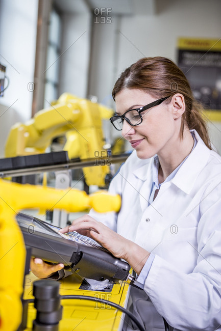 Woman using device in factory with industrial robots