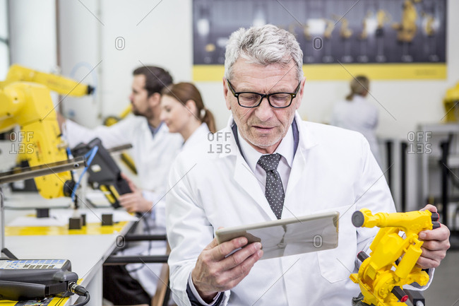Engineer holding tablet and model of an industrial robot