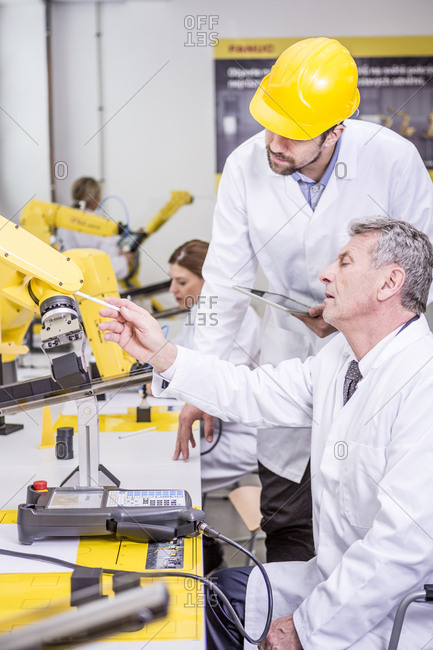 Two engineers examining industrial robot