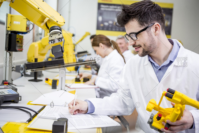 Engineer in factory holding model of an industrial robot taking notes on clipboard