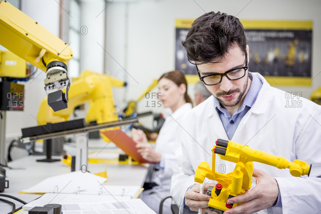 Engineer holding model of an industrial robot