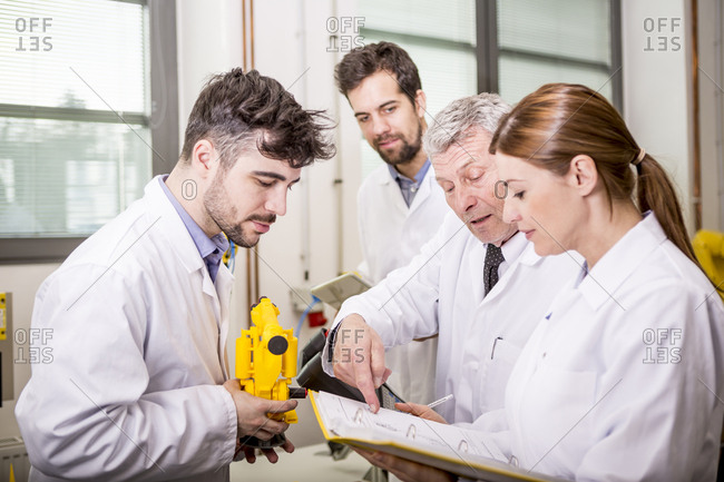 Engineers with industrial robot model checking documents