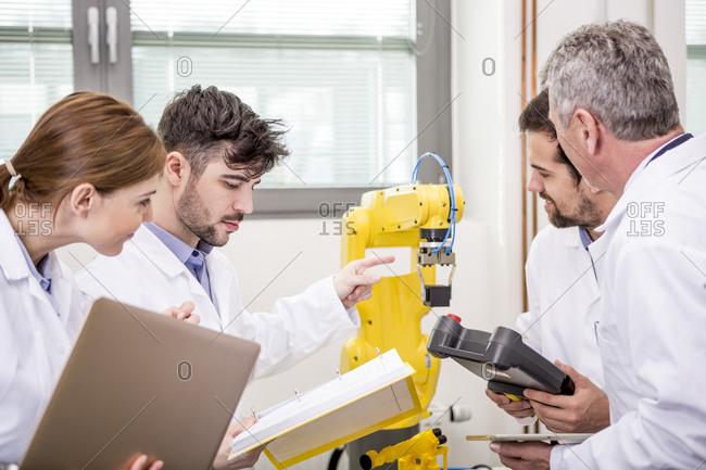 Engineers examining industrial robot