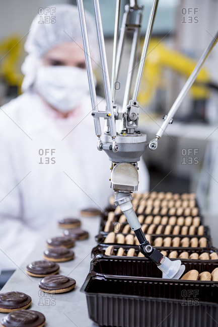 Woman in factory looking at robot handling cookies