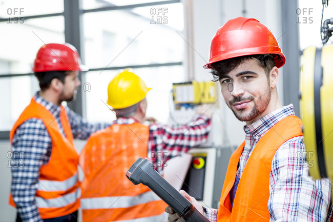 Portrait of confident man wearing hard hat in factory