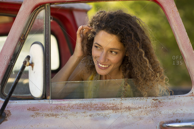 Happy young woman fixing her hair in car mirror