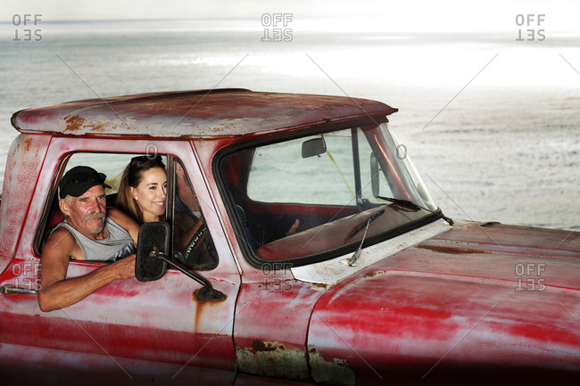 Senior man and young couple in an old pick up at the coast