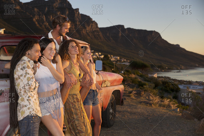 Young people outside pick up truck at the coast enjoying the sunset