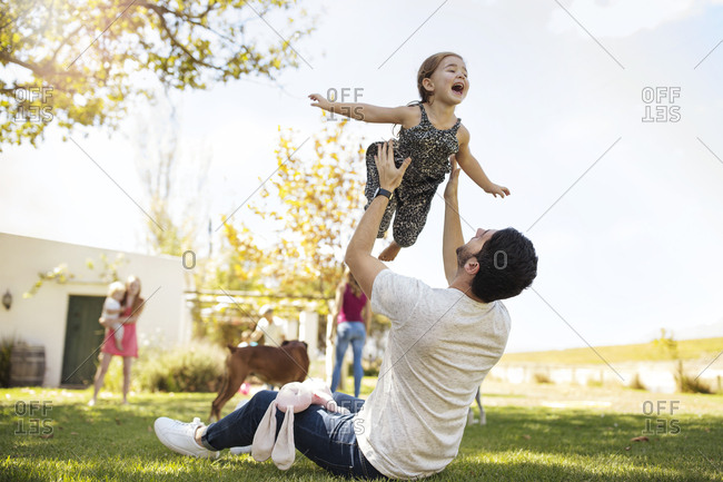 Father playing with daughter in garden