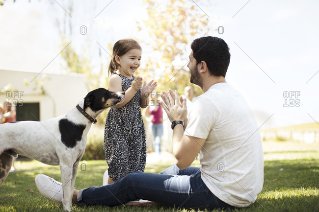 Happy father- daughter and dog in garden