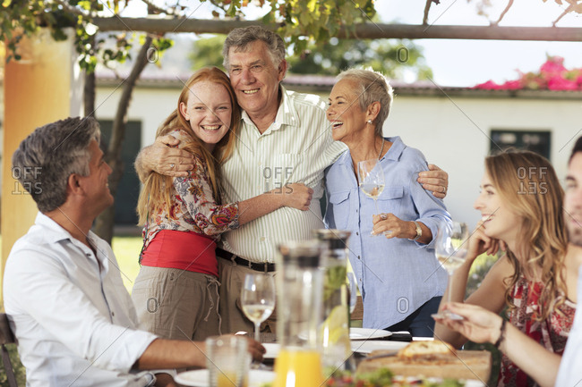 Happy senior couple with family having lunch together outside