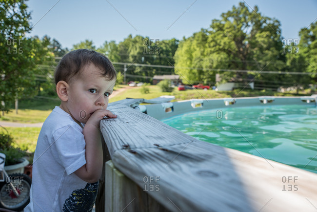 Toddler looking over ledge of swimming pool