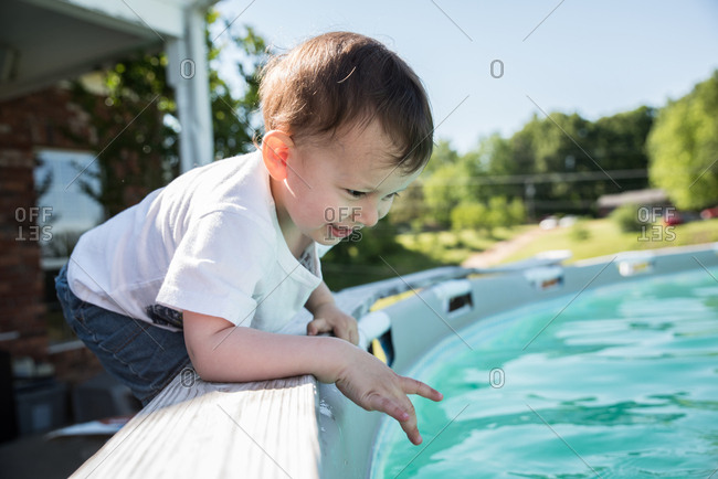 Toddler climbing on ledge of swimming pool