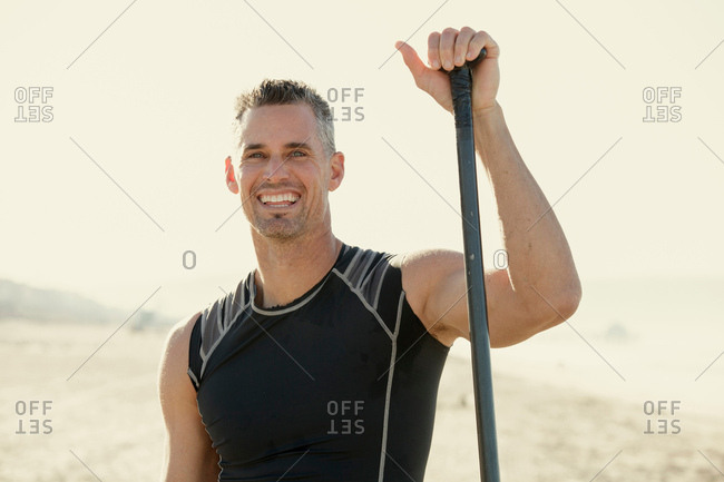 Mid adult man surfer standing with surf paddle on beach, portrait