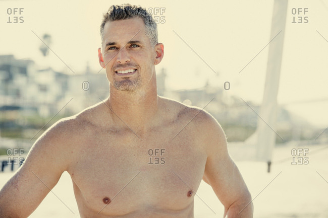 Shirtless mid adult man on beach, smiling
