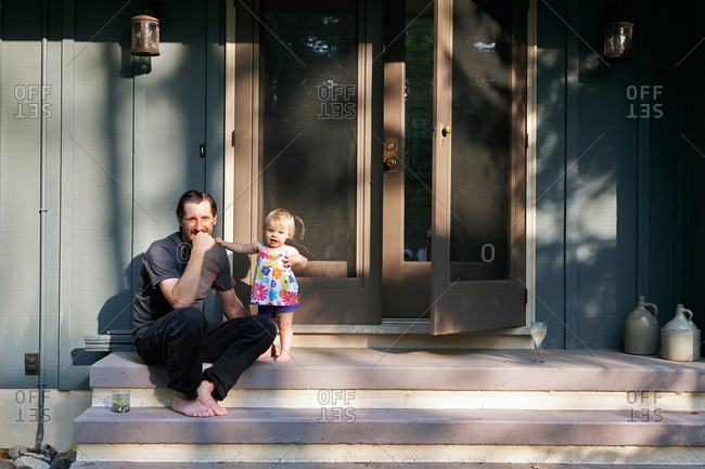 Mature man sitting on steps with young daughter, portrait