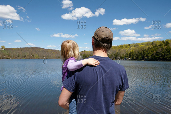 Father and daughter looking at lake, rear view