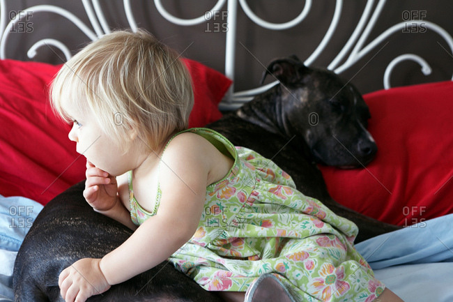 Girl leaning on dog on bed and looking away